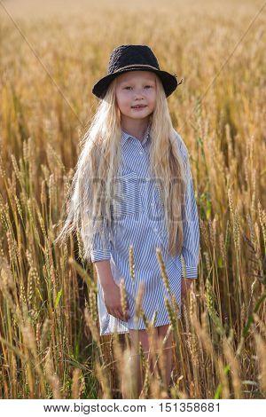 happy little blonde girl in wheat field with long hair
