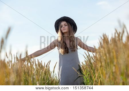 young beautiful woman wearing hat in golden wheat field