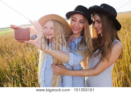 beautiful young mother and her daughters at the wheat field on a sunny day doing selfie