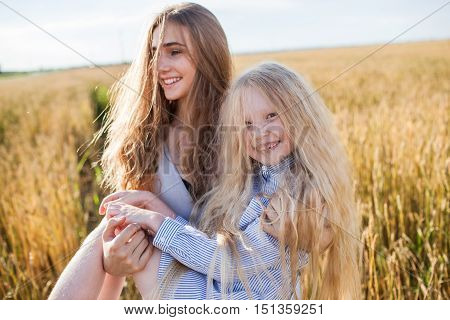 One sister carries another in a wheat gold field