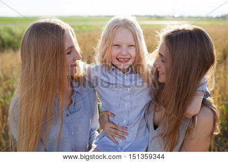 beautiful young mother and her daughters at the wheat field on a sunny day, little girl in center
