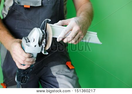 angle grinders in the hands of the builder. industrial tool, hand grinder cutting plastic