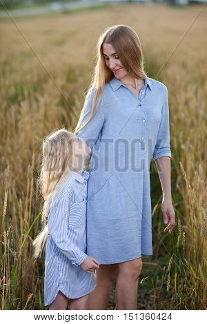 beautiful young mother and her daughter at the wheat field on sunset