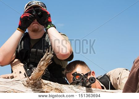 One officer scoping out the area with binoculars while the second man focuses the target in his site