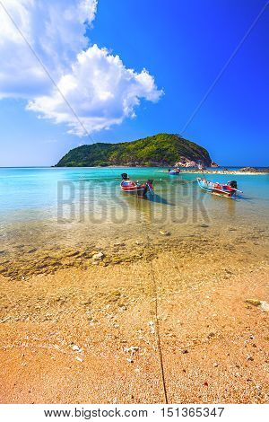 Green island and the turquoise sea water with colorful wooden boats off the coast.