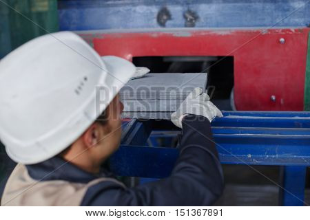 Male factory worker pulls out a lime-ash brick press machine