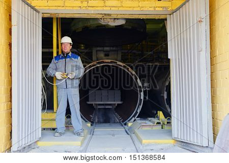 Portrait of factory worker in overalls and helmet with a remote control in hand on the background of kiln brick
