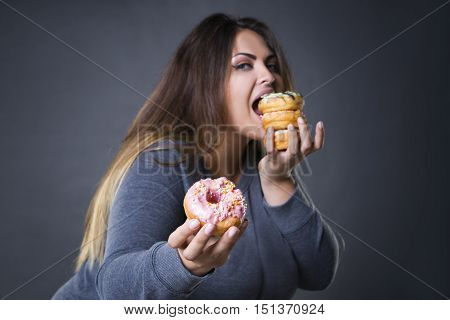 Happy beautiful young caucasian plus size model posing with donuts on a gray studio background fast food and unhealthy nutrition concept