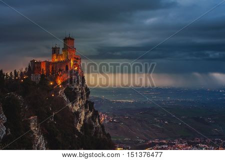 San Marino fortress of Guaita on Mount Titano at sunset. Heavy raining clouds with aerial view at the city. Car traffic lights and illumination
