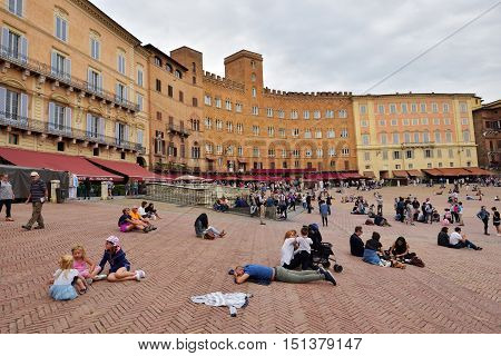Siena, Italy - October 1, 2016: Tourists and spectators inside Piazza del Campo in a cloudy day, Siena, region of Tuscany, Italy