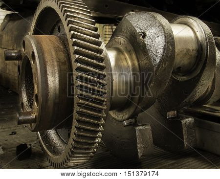 Close up of a crank shaft out of truck engine showing cog and camshaft.