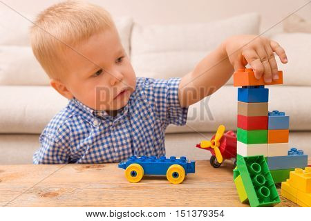 Portrait of child playing with colorful plastic bricks at the table. Toddler having fun and building a train out of constructor bricks. Early learning. Developing toys