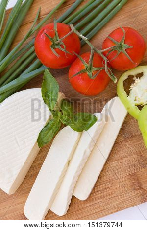Homemade soft cheese Suluguni with tomatoes paprica onions and fresh basil on a wooden board. Healthy food concept