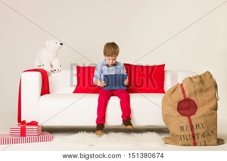Portrait of cute kid boy sitting on whote sofa and playing with computer tablet. Child with PC during Christmas time. Holidays seasons.