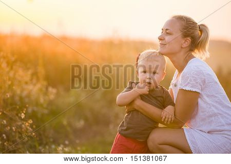 Young beautiful mother hugging her little toddler son on a sunset in a wild flowers field. Happy woman with her baby boy on a summer sunny day. Family walking on the meadow.