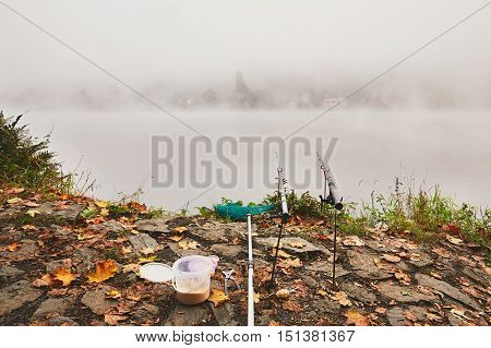 Fishing rods landing net and bait fishing on the river bank. Thick fog during autumn morning in beautiful nature in the Czech Republic