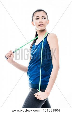 Fit young Asian woman with a skipping rope slung around her neck standing looking back over her shoulder with a pensive expression, three-quarter isolated on white