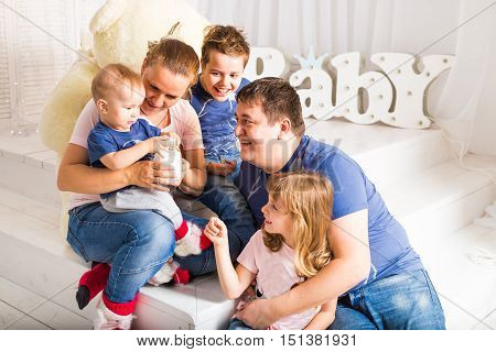 Happy family with 3 children sitting on floor of living room at home.