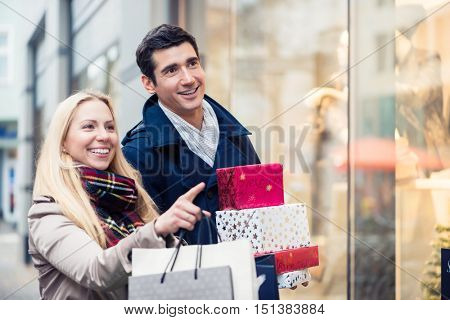 Couple at shop window doing Christmas shopping