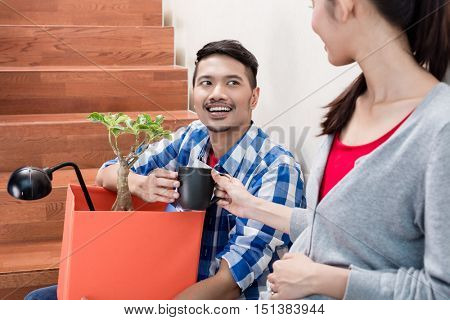 Indonesian couple, woman and man, taking coffee break in the stairway during relocation between moving boxes