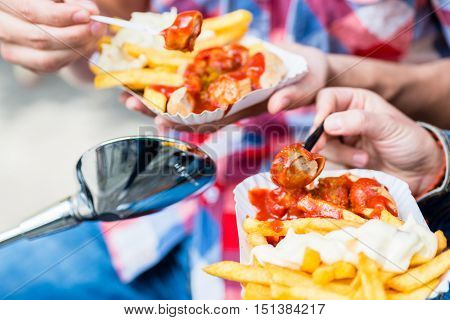 Man and woman eating german specialty Currywurst and french fries on scooter