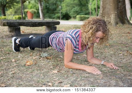 Fit Blonde Senior In Plank Position Park On A Sunny Day