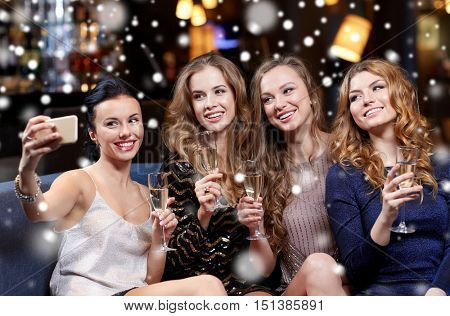celebration, friends, bachelorette party, technology and christmas holidays concept - happy women with champagne and smartphone taking selfie at night club over snow