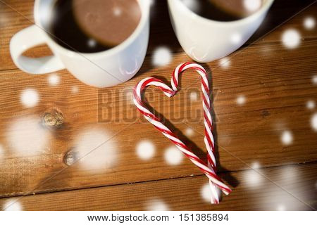 holidays, christmas, winter, food and drinks concept - close up of candy canes and cups with hot chocolate or cocoa drinks on wooden table