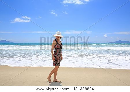 Young pretty smiling woman in a hat is strolling along Sandy Beach. Waipu Area Northland North Island New Zealand
