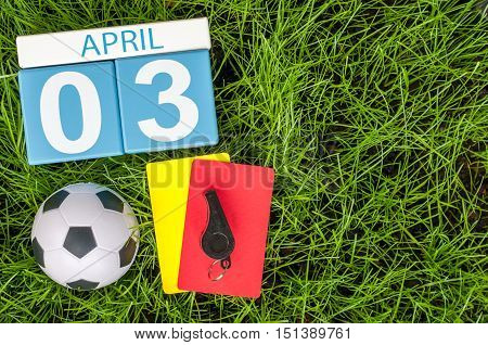 April 3rd. Day 3 of month, calendar on football green grass background. Spring time, empty space for text.