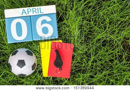 April 6th. Day 6 of month, wooden color calendar on football green grass background. Spring time, empty space for text.