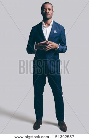 Confident in his style. Full length of handsome young African man in full suit holding hands clasped and looking at camera while standing against grey background