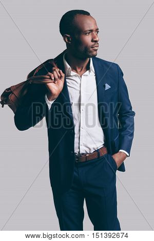 Stylish and handsome. Handsome young African man in full suit carrying brown leather bag on shoulder and looking away while standing against grey background