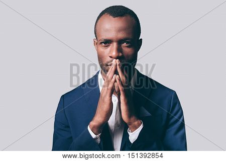Elegance and masculinity. Portrait of thoughtful young African man in smart casual jacket holding hand clasped near face and looking at camera while standing against grey background