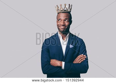King? Handsome young African man in crown and smart casual jacket making a face while standing against grey background