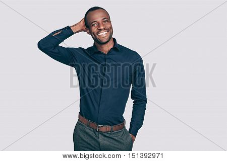 Cheerful and handsome. Handsome young African man holding hand behind head and smiling while standing against grey background
