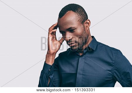 Feeling uncertain. Handsome young African man touching head with hand and looking uncertain while standing against grey background