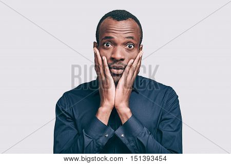 Oh no! Frustrated young African man touching head with hand and looking at camera while standing against grey background