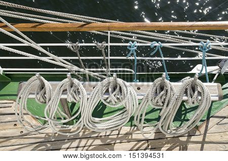 White ropes wrapped around belaying pins in sailing ship
