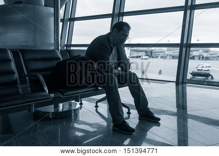 Sad man waiting for delayed flight in airport