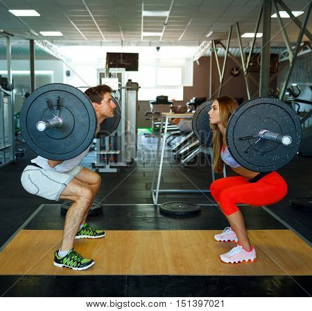Athletic couple - man and woman with barbell doing squats in the gym