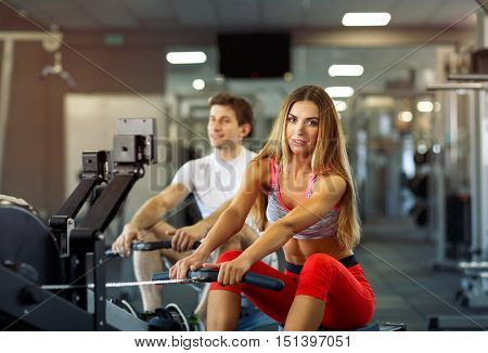 Athletic couple - man and woman training on row machine in gym