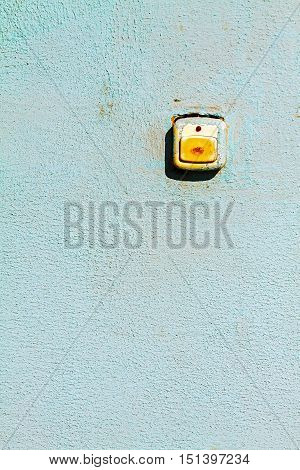 The old button doorbell on the plastered wall.