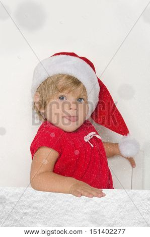 little girl in Santa suit in falling snow on gray background