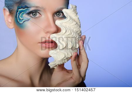 woman in make mermaid with seashell on blue background