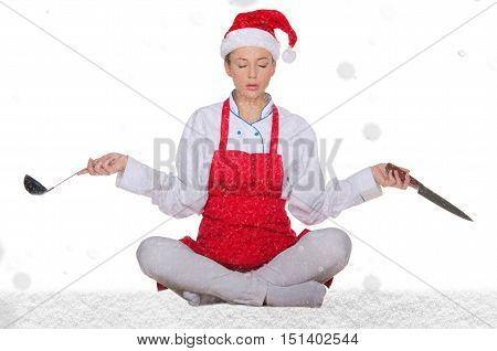 Cook in Santa Claus hat yoga knives and snow on white background