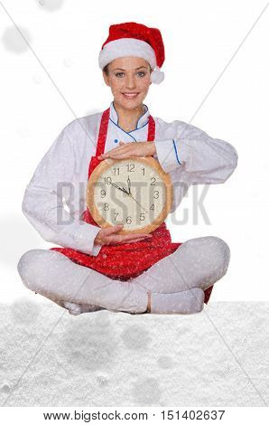 Woman cook in Santa hat yoga clock under snow on white background