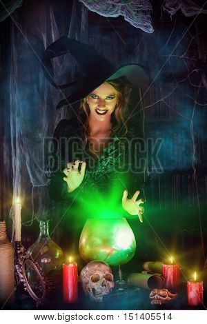 Attractive witch conjures in the wizarding lair. Fairytales. Halloween.