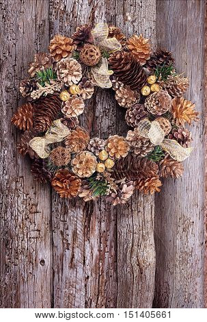 Christmas wreath in gold tones on the old wooden textured wall with copy space