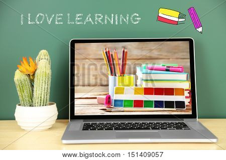 Laptop with stationery wallpaper on screen against chalkboard. Text I LOVE LEARNING on background. School teacher concept.